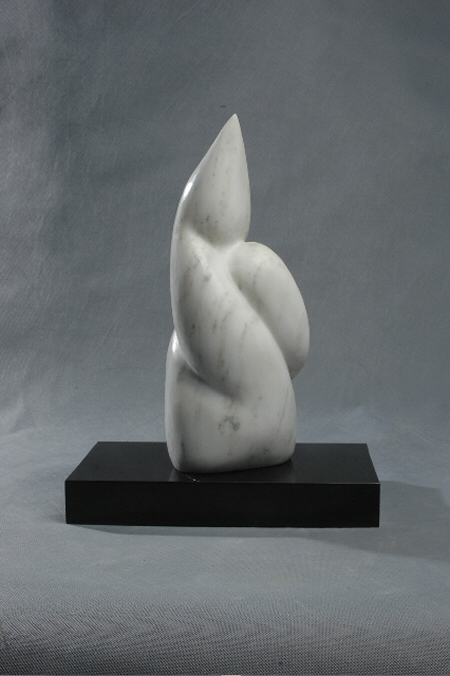 small abstract sculpture in white marble, reminiscent of an earth form