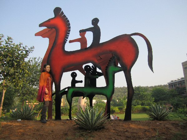 Sculptor Zhang Yaxi next to her completed equestrian sculpture installation in painted steel