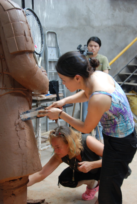 Chinese sculptor Zhang Yaxi working on the Roger Federer tennis terracotta warrior sculpture in Chonqging for the Tennis Master Cup Shanghai 2007 along with fellow sculptor Laury Dizengremel